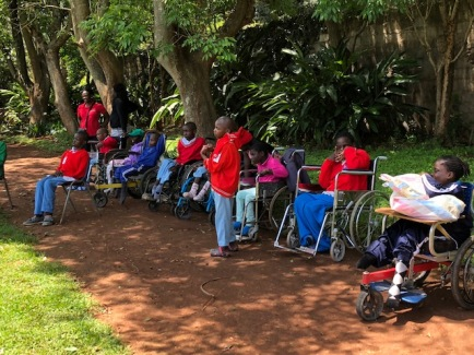 the disabled children on their wheelchairs sitting in shade